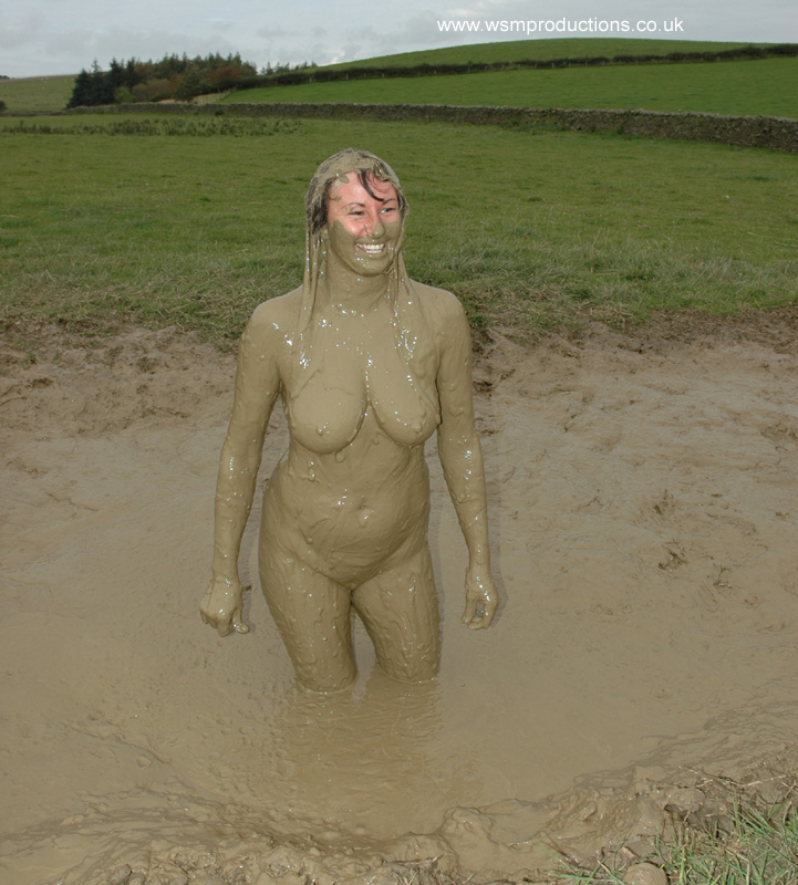 Nude women playing in mud